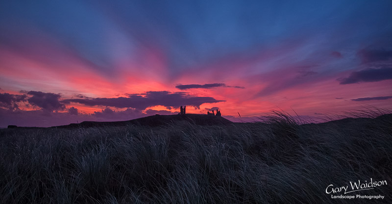 Dunstanburgh castle at sunrise. Landscape photography by Gary Waidson.